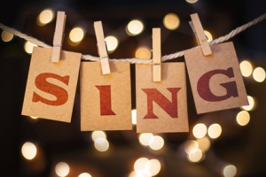 The word SING printed on clothespin clipped cards in front of defocused glowing lights.